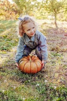 屋外で巨大なカボチャを育てようとしている子供の子供の女の子。ファームガーデンでデニムスーツを着た白人の金髪の少女の子供たちの手で秋の通りのハロウィーンのカボチャ。
