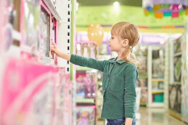 Kid choosing toys for purchase in big store.