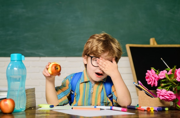 Kid in class room with blackboard on background kid boy from primary school first day of school back
