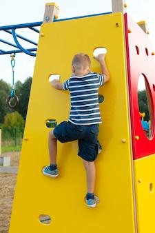 매력 놀이터에서 벽에 등반 하는 아이.