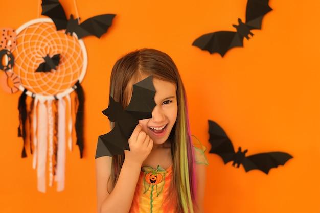 할로윈 장식으로 격리된 주황색 스튜디오 배경에 박쥐로 한쪽 눈을 감고 있는 아이