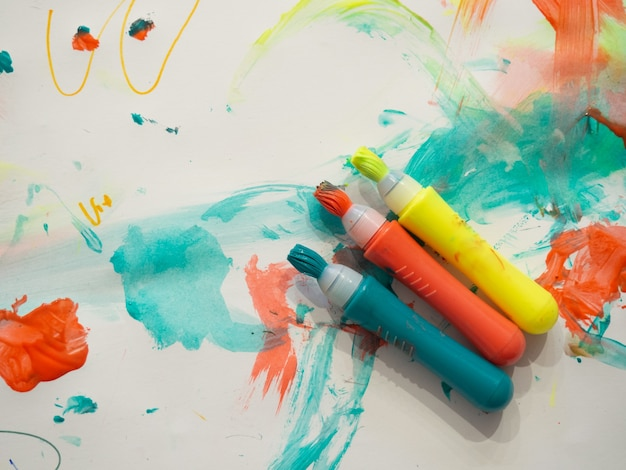 塗られた白い紙の背景にブラシストロークラインを持つキッドカラーマーカーマクロ選択的フォーカス