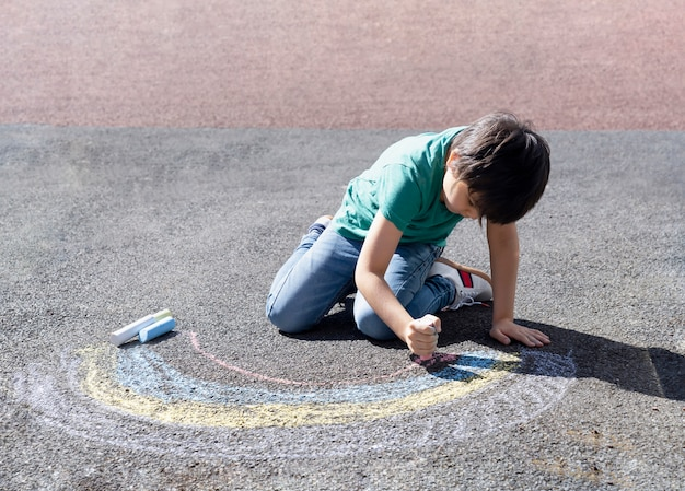 Kid colouring rainbow on pavement, child drawing rainbow with colorful chalks on footpath during covid-19 quarantine at home