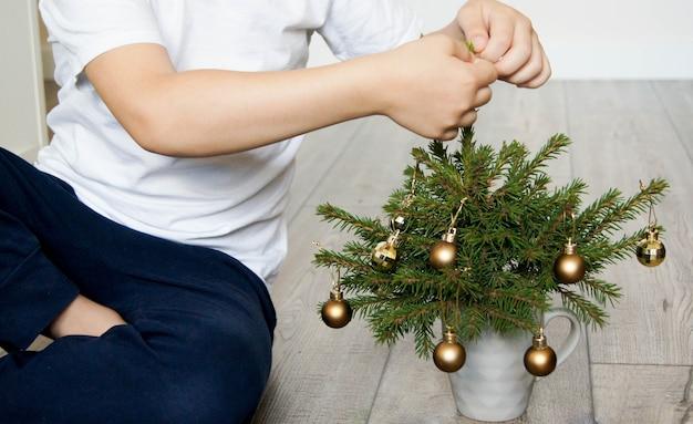 子供は小さな金のボールで小さなクリスマスツリーを飾ります