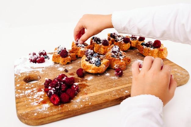 신선한 딸기로 케이크를 장식하는 아이