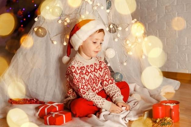 クリスマスツリーを飾る子供新年それは奇跡です