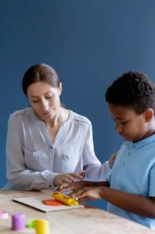 Ребенок делает сеанс трудотерапии с психологом
