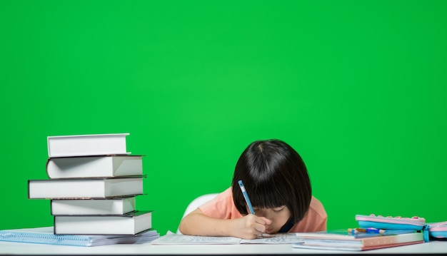 Kid doing homework on green screen, child writing paper, education concept
