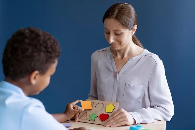 Bambino che fa una sessione di terapia occupazionale con uno psicologo Foto Gratuite