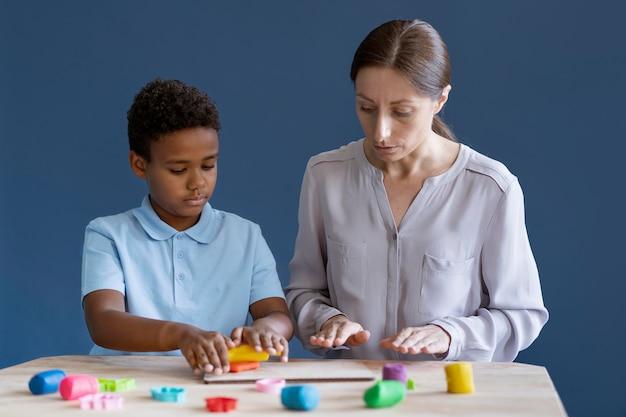 Bambino che fa una sessione di terapia occupazionale con uno psicologo