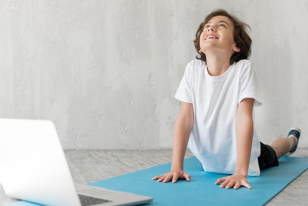 Малыш занимается спортом рядом с ноутбуком