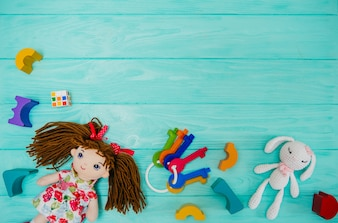 Kid doll with wooden building blocks on blue background