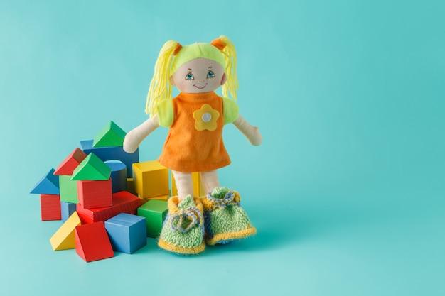 Детские куклы с деревянными строительными блоками на простом фоне
