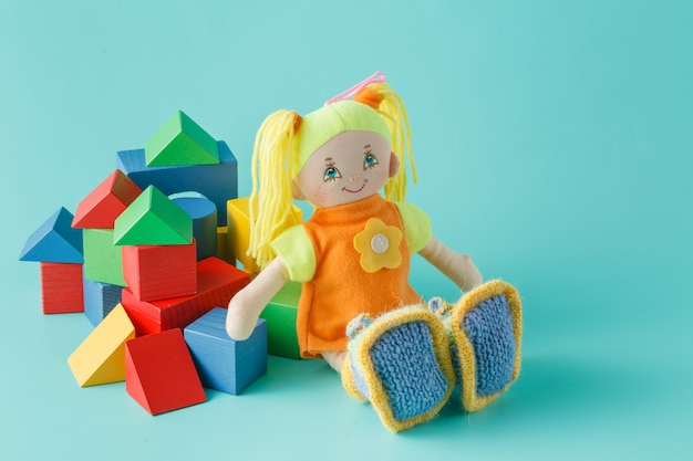 Kid doll with wooden building blocks on plain background