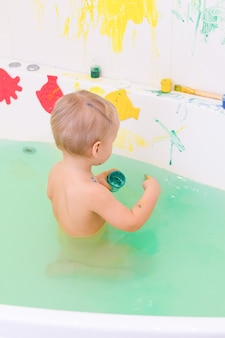 Kid draw with paints in the bath