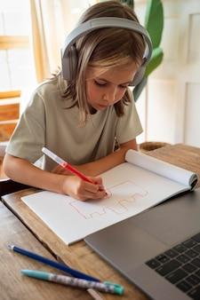 Bambino che disegna a casa inquadratura media