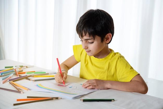 Малыш рисует свою семью на листе бумаги цветными карандашами. понятие детской психологии