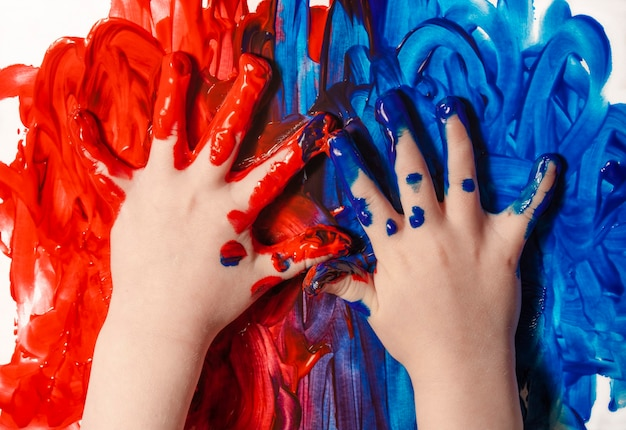 The kid draws with his hands the first drawing with paints art and creative education concept