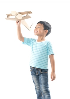 Kid dreams as pilot standing and holding airplane paper isolated on white
