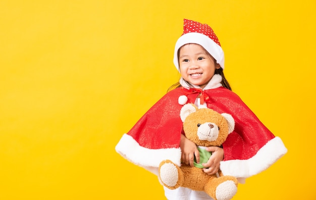 Kid dressed in santa claus hat hugging teddy bear the concept of christmas xmas day