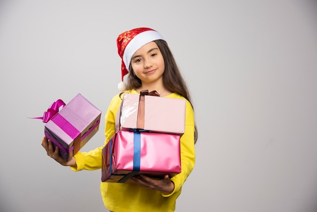 Kid dressed in santa claus red hat carrying a lot of christmas presents. high quality photo