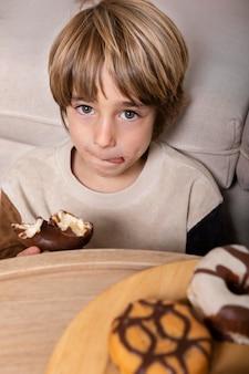 집에서 도넛을 먹는 아이