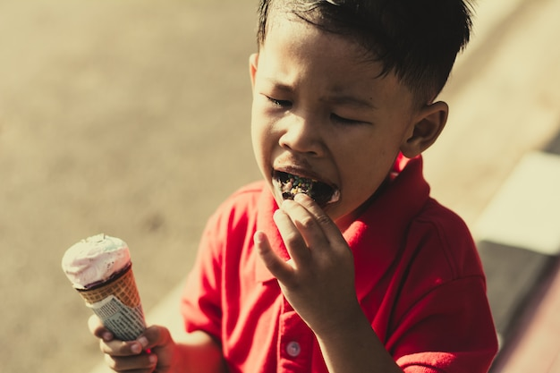 Kid eating ice cream in waffles cone and winking on park outdoor background.
