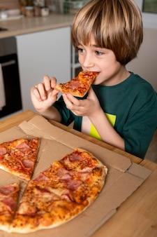 Bambino che mangia pizza a casa
