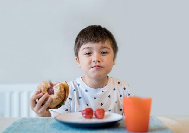 Ребенок ест цельнозерновые бублики на завтрак, школьник ест здоровый пончик ребенок ест хлеб и сок пить на завтрак. концепция здоровых детей