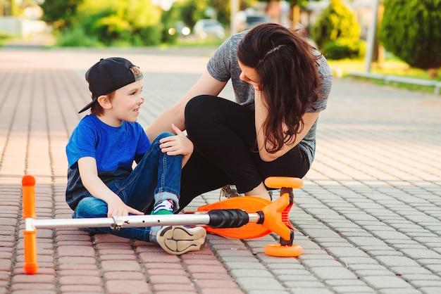 スクーターに乗ることを学んでいる間、子供は倒れました。