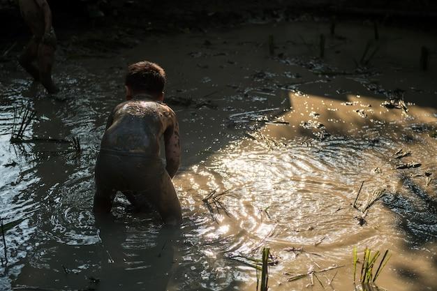 어린이 농부는 논 쌀 묘목을 물 진흙 농장에 재배하거나 심습니다.