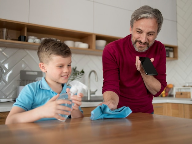 Kid and father cleaning table