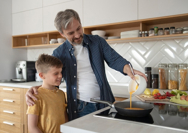 Kid and father cooking in kitchen