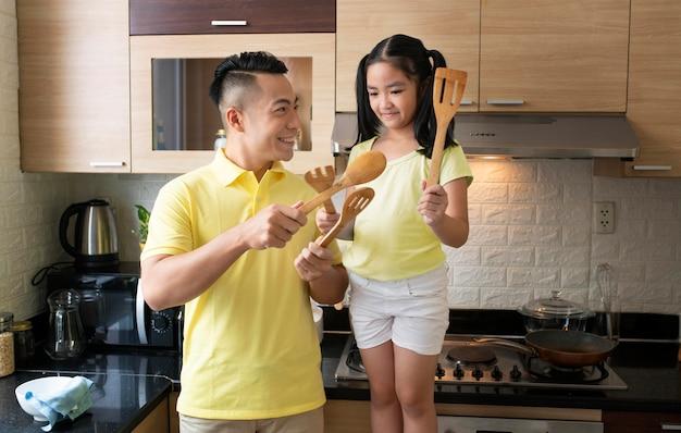 Bambino e padre che tengono gli utensili da cucina