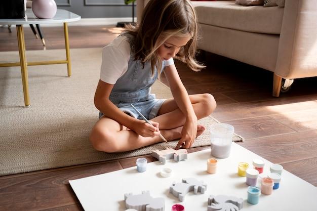 Kid on floor painting full shot