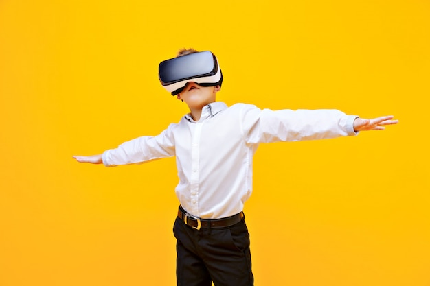 Kid in formal outfit wearing vr glasses putting hands out in excitement isolated