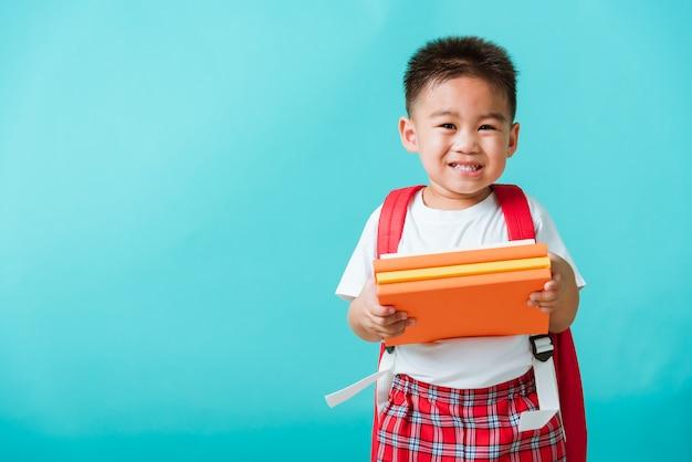 Kid from preschool kindergarten with book and school bag