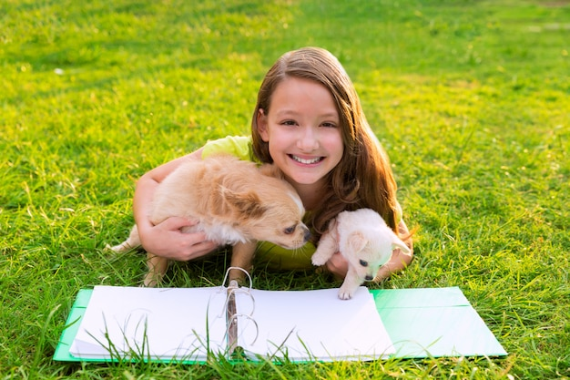 子供の女の子と芝生で横になっている宿題で子犬犬