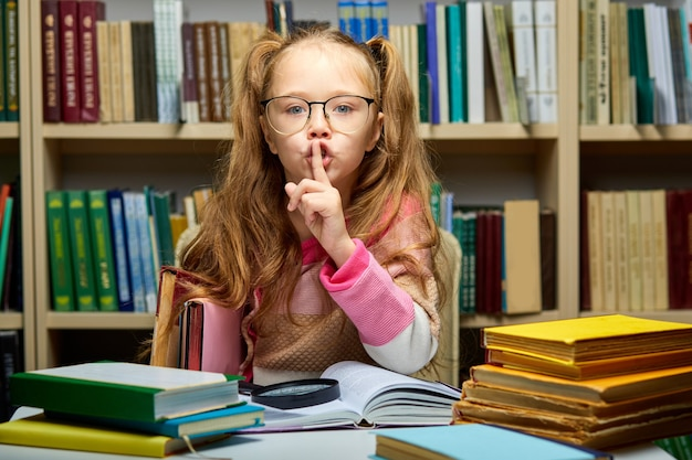 Kid girl asks to be quiet in library, school child sits alone at table with books, holding one finger on mouth, keep silence concept