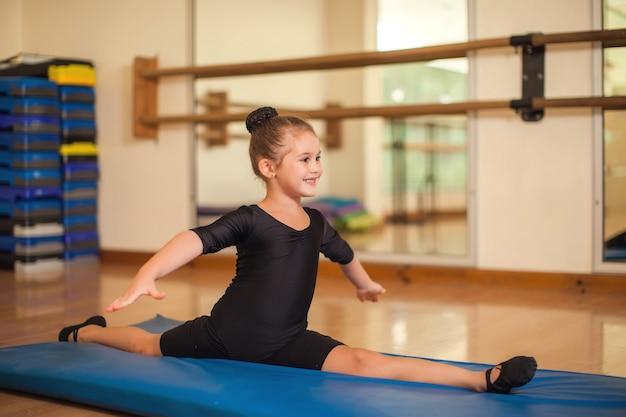 Малыш девочка в классе гимнастики, делая упражнения. дети и спортивная концепция