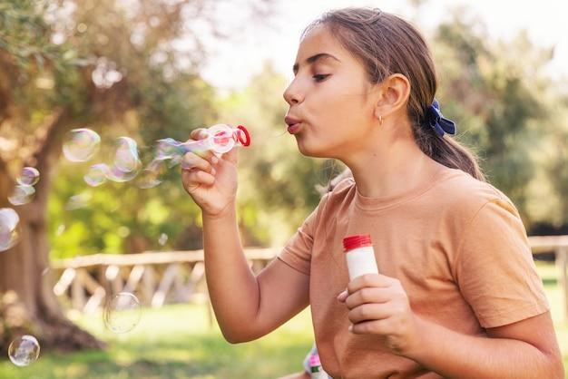 Kid girl пускает мыльные пузыри в парке летом
