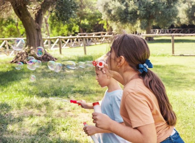 Kid girl and boy blowing soap bubbles in a park