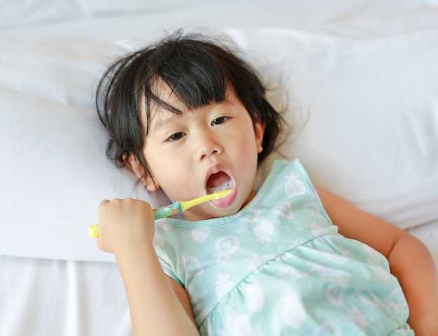 Kid girl brushing teeth on the bed at morning