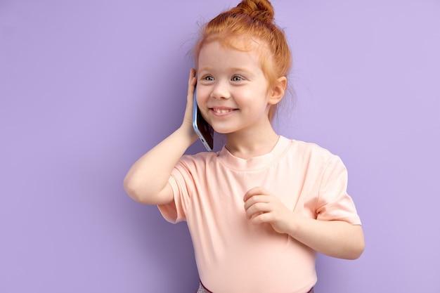 꼬마 소녀는 휴대 전화, 미소 및 격리 회담에서 통신합니다. 근접 촬영 웃는 아이 스마트 폰 이야기. 사람들이 성실한 감정 라이프 스타일 개념