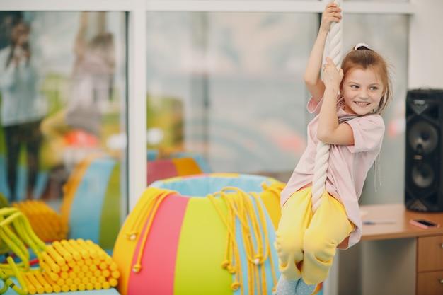 幼稚園や小学校の体育館で綱渡りの練習をしている女の子。子供のスポーツとフィットネスの概念。