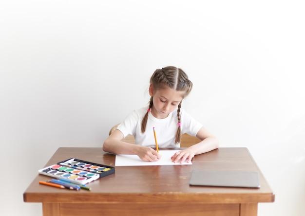 テーブルに座って家で絵を描いたり絵を描いたりする子供の女の子