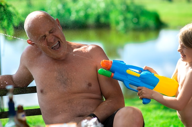 Kid girl and grandfather playing with water gun toy in the summer.
