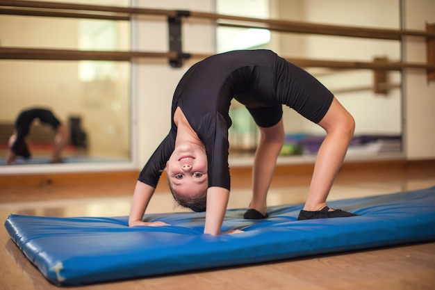 Kid girl at gymnastic class doing exercises. children and sport concept