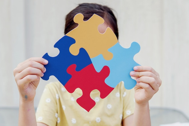 Kid girl hands holding puzzle jigsaw,  mental health concept, world autism awareness day