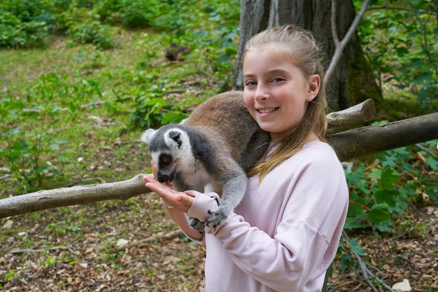 Kid girl having fun with ring tailed lemur animal